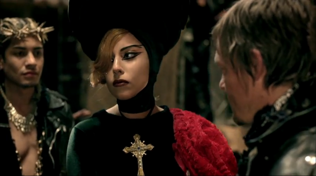 Lady Gaga with giant red and black orbicular hat, vaguely reminiscent of a harlequin or jester, holding a Golden Gun between Jesus and Judas in a moment of tension.