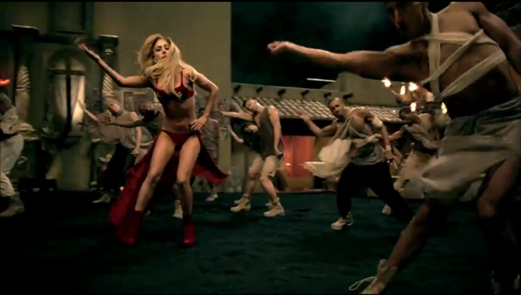 Lady Gaga wearing a red bikini top with a white crucifix on the center of each cup, and half of a red skirt - dancing with backup dancers in fairly bland modified athletic clothing.