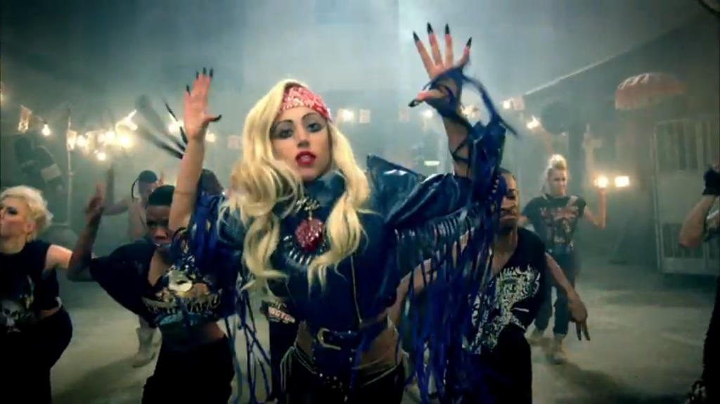 Lady Gaga in a blue leather outift with blue fringe and a sacred heart on her chest; a red paisley bandanna holding back her blonde hair, and long blue nails that come to points.