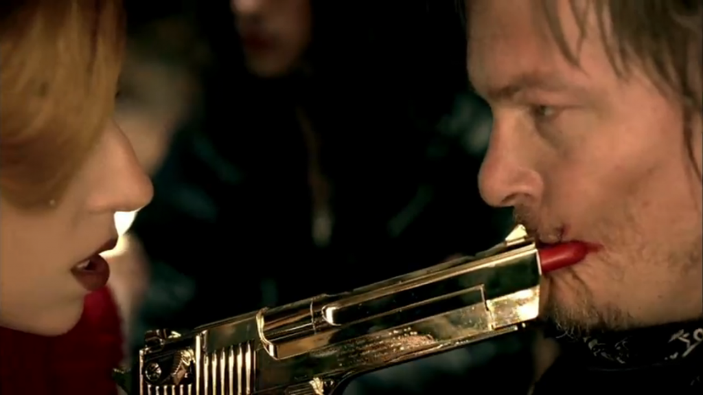 Lady Gaga smearing the lipstick point of the gun on the face of Judas, both of them looking intense.