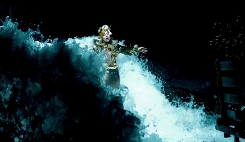Lady Gaga standing in a cave in a dark metallic gold frock, a fuggled chest piece and her hair up in a bun, standing in water.