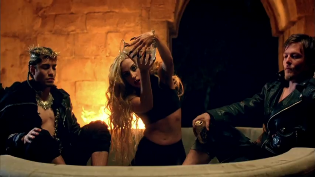 A scene with Jesus on the left, Lady Gaga in the middle, and Judas on the right of a giant stone tub with a deep bowl.