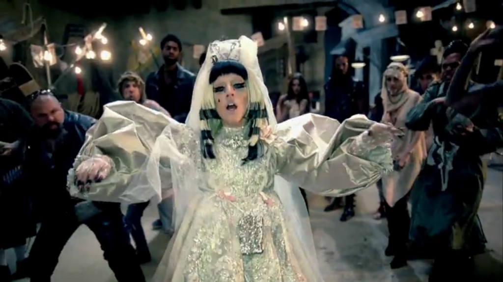 Lady Gaga with black hair with blond stripes, in a wedding dress, possibly pregnant, being stoned by a crowd of angry people.