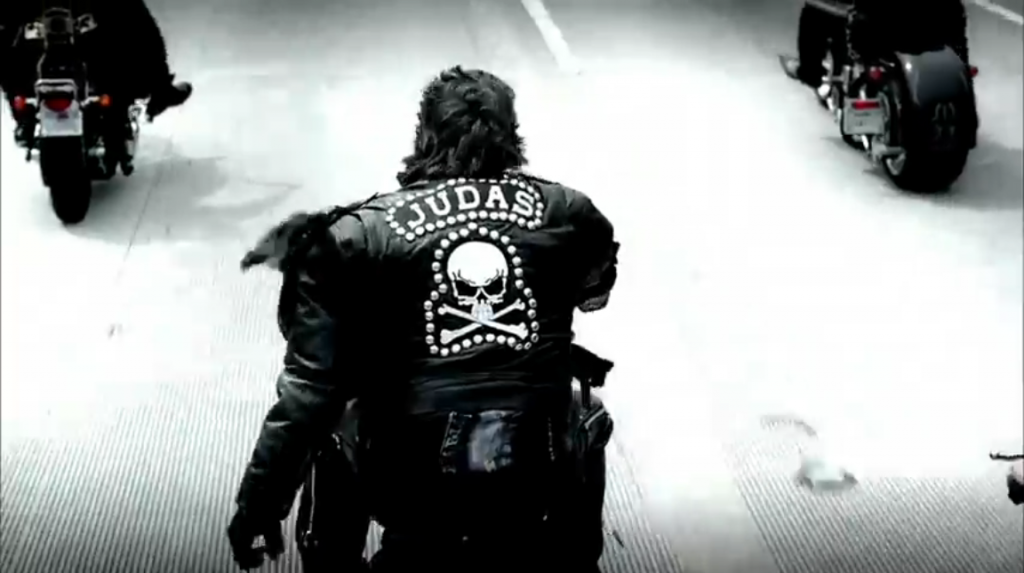 Shot of one of the men on the motorcycles with JUDAS on the back of his leather jacket in white letters with a skull beneath it, both of which are surrounded by a border that looks like metal studs or rhinestones