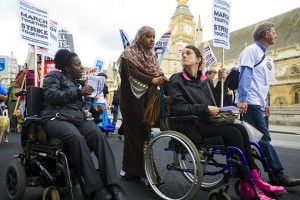 Two wheelchair-using protesters, one of whom appears to have a personal assistant, at a protest in Britain. Photo by Martin Argles for The Guardian.
