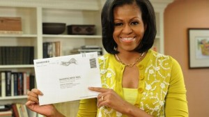 Michelle Obama holds up her absentee ballot, ready to mail
